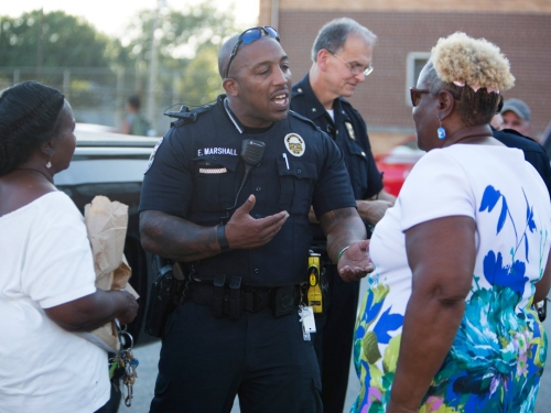 Police officers meet with community leaders.
