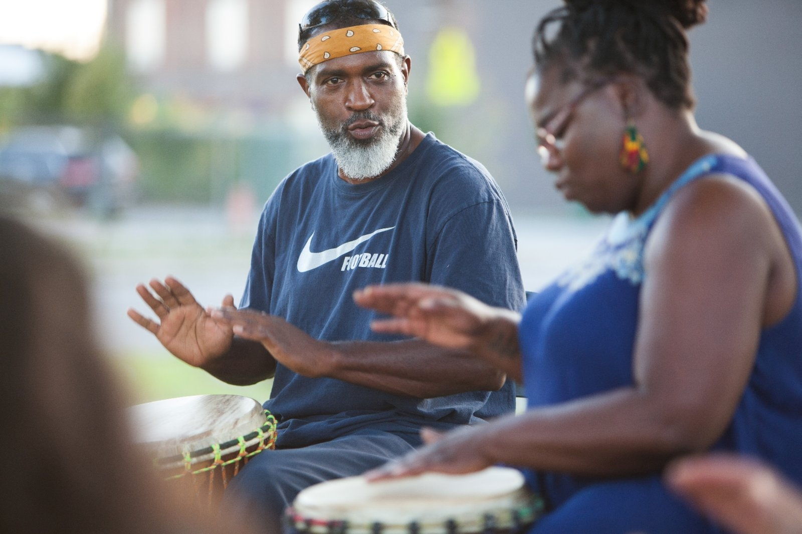 Community members play in a drum circle.
