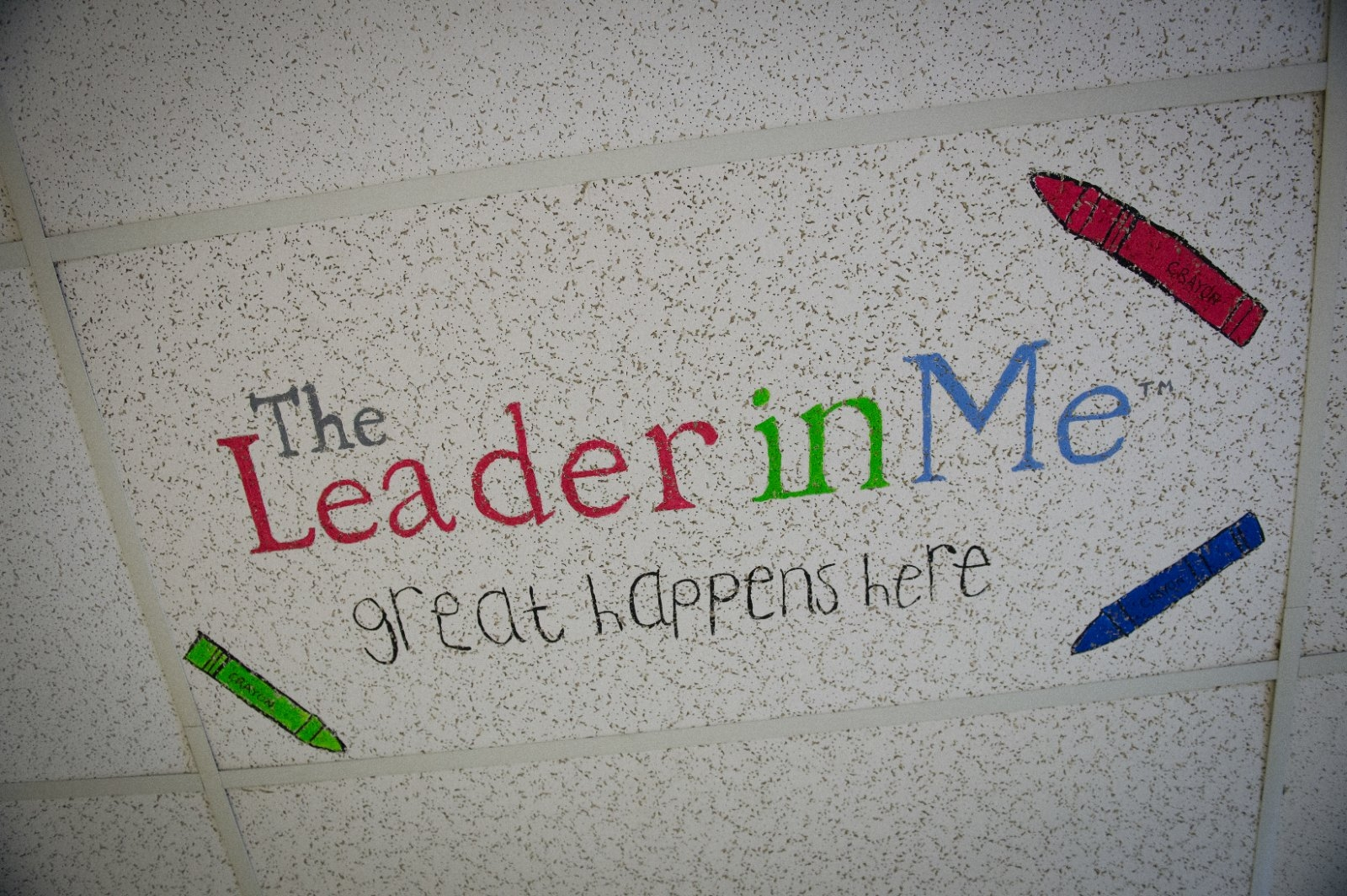A ceiling tile promoting a leadership campaign in a school.