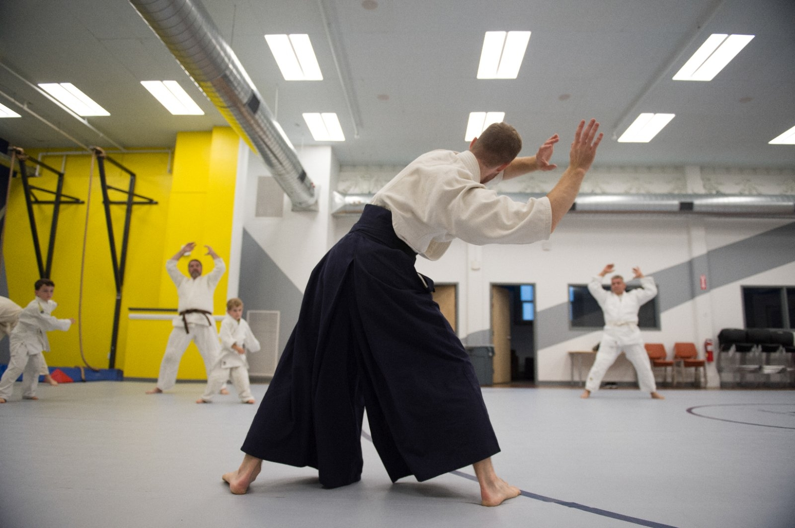 An instructor and student practice aikido.