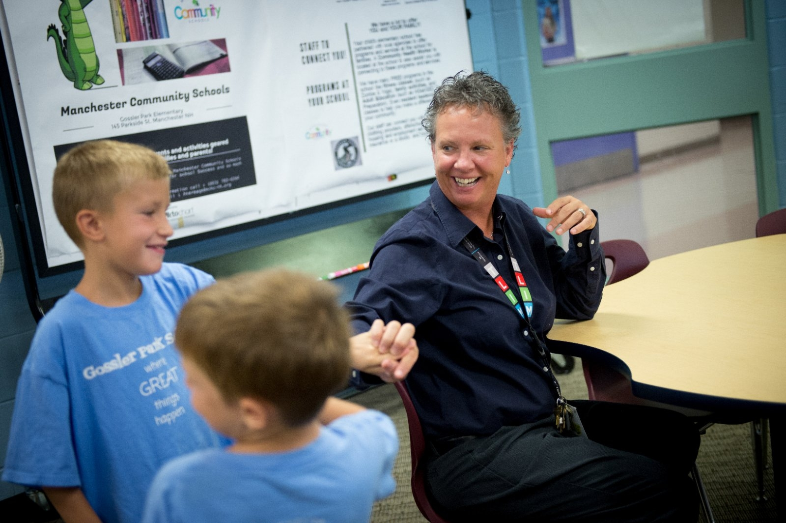 A school principal talks and laughs with elementary school students.