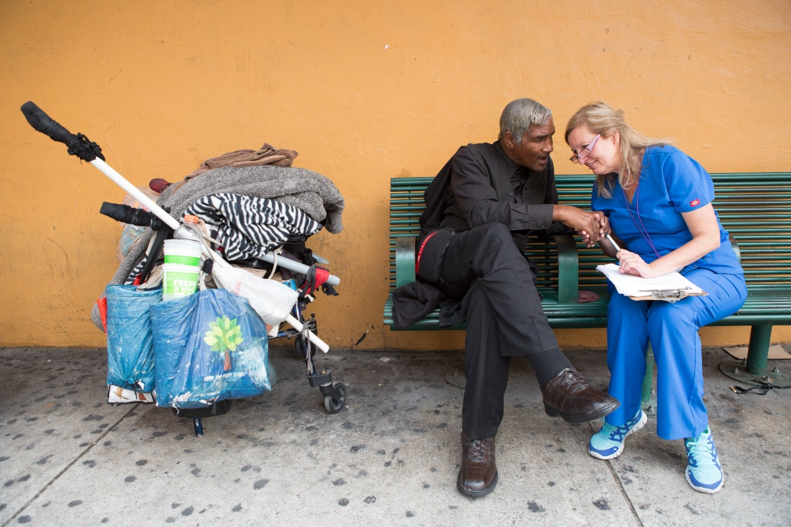 An outreach health worker speaks with a homeless man.