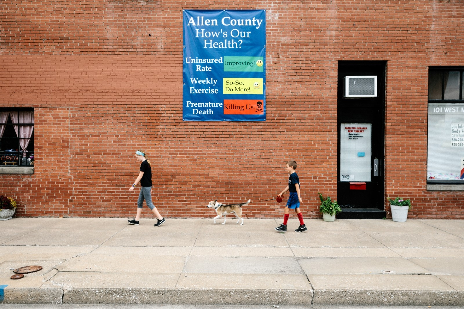 Siblings walk their dog down a city block in downtown Iola, KS.