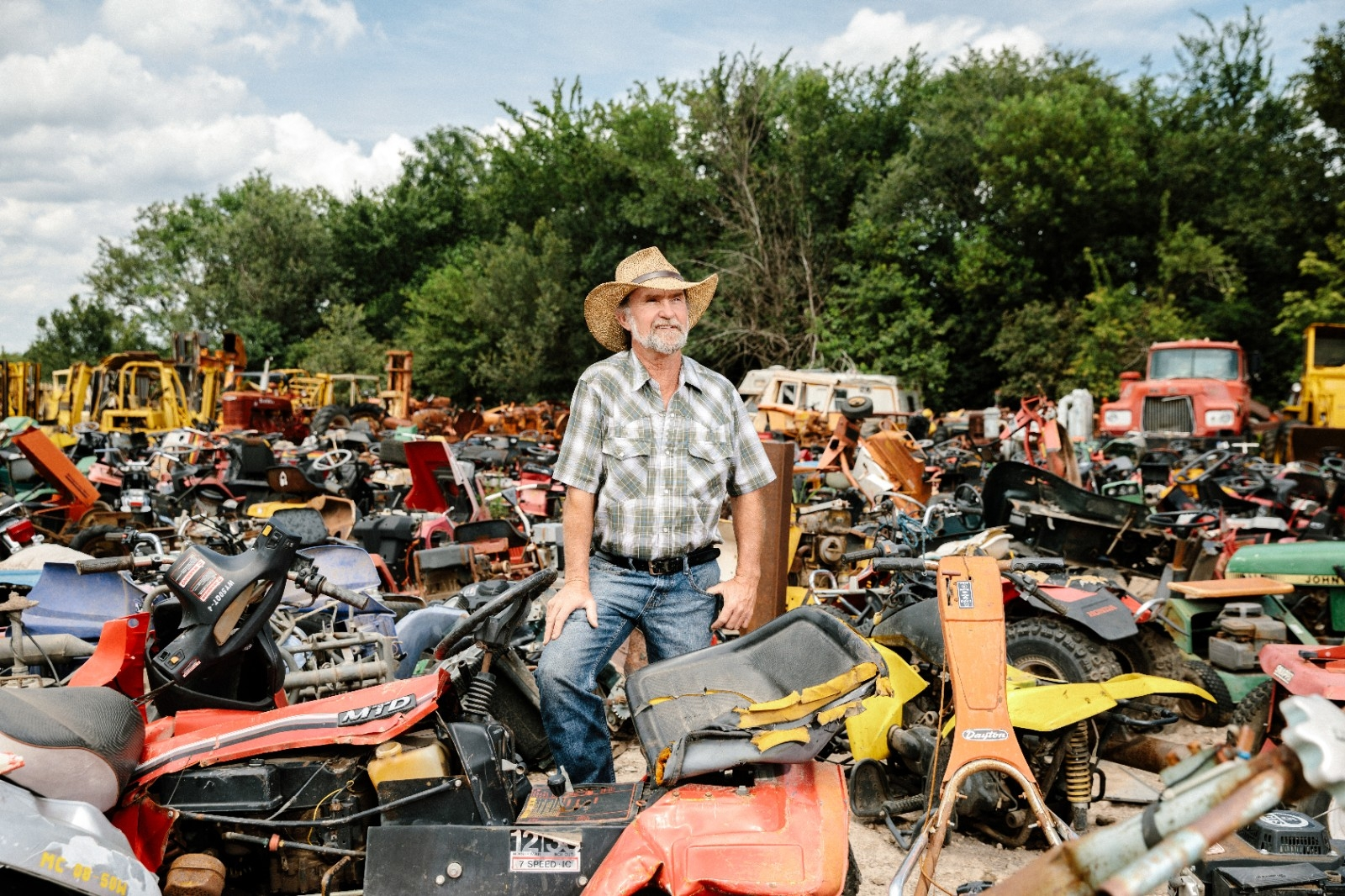 Owner stands near some scrap material in his junkyard and auto salvage business.