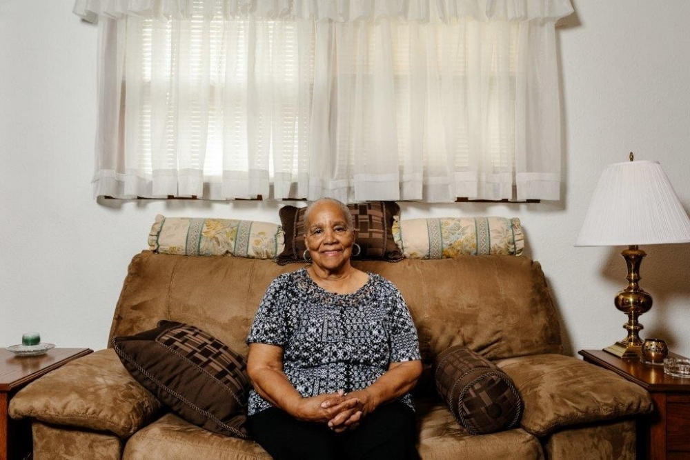 A smiling woman sits in her living room.