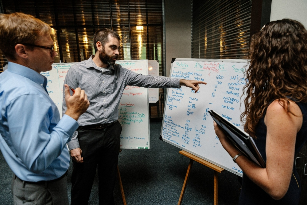 Young professionals review information on a white board.
