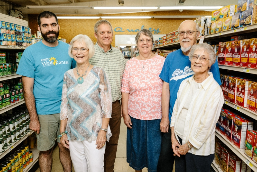 A group of citizens stand in local grocery store aisle.