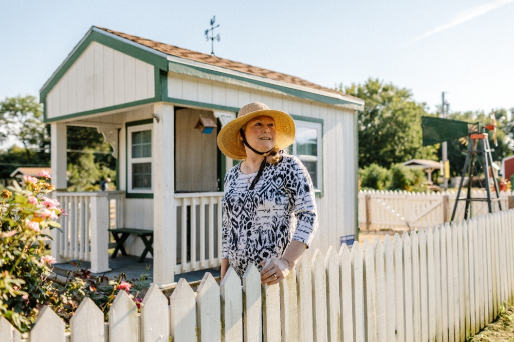 A woman in sun hat stands next to a garden shed.