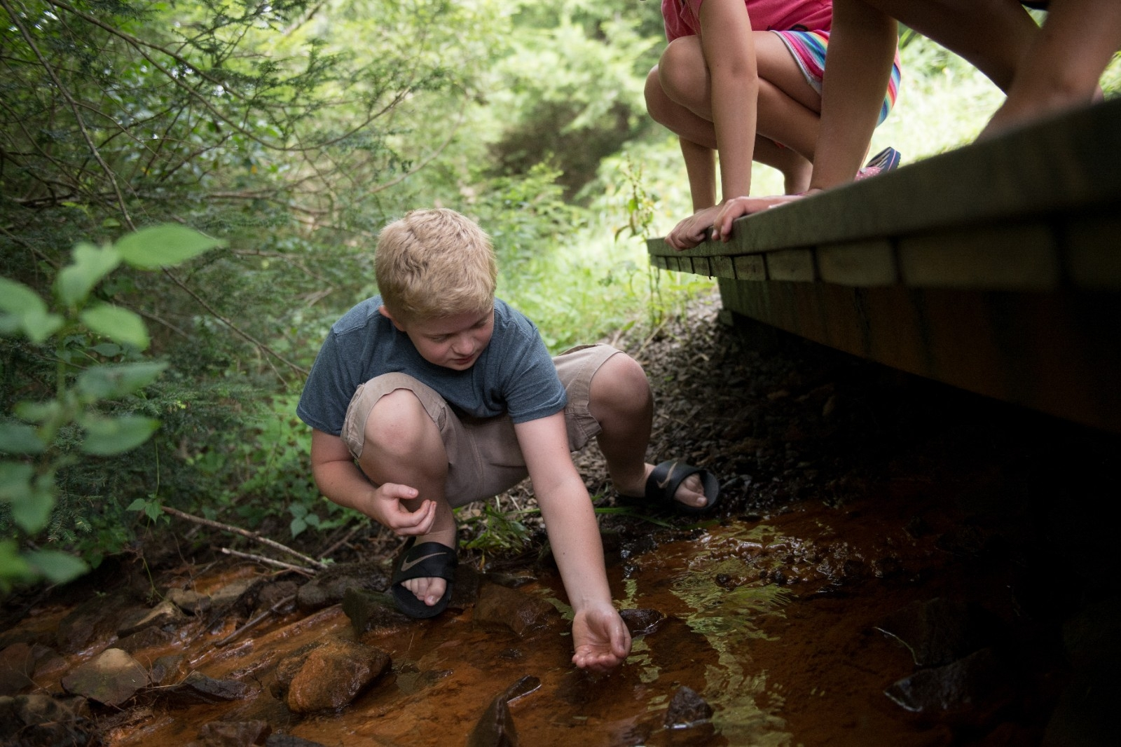 Student examines the creek water behind his elementary school.