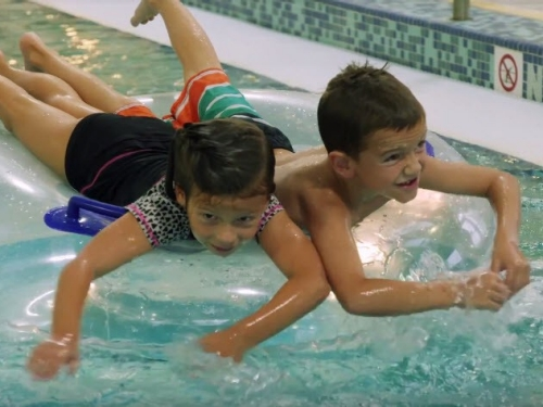Two kids on a raft in a community pool.