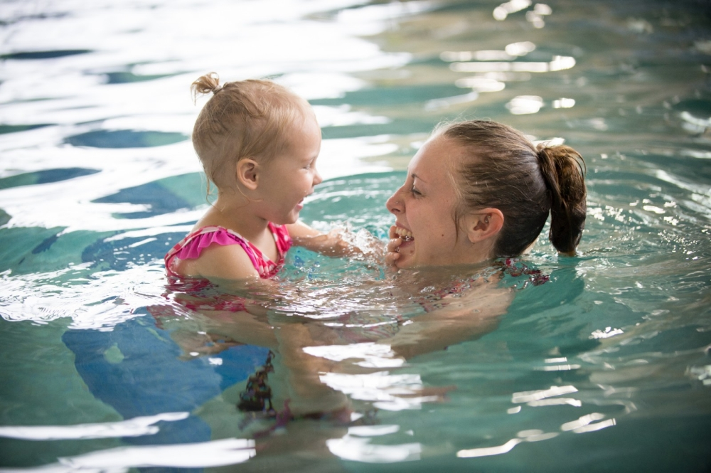 Mother swims with daughter in community pool.