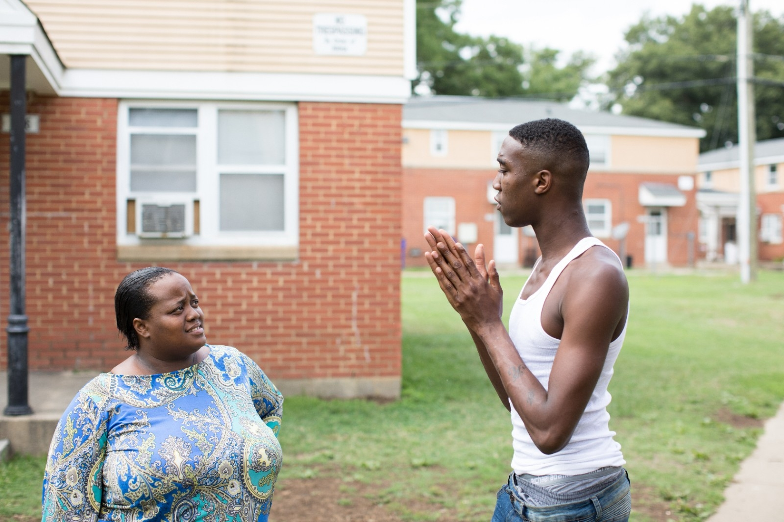 Two people have a discussion in the front yard of an apartment building.