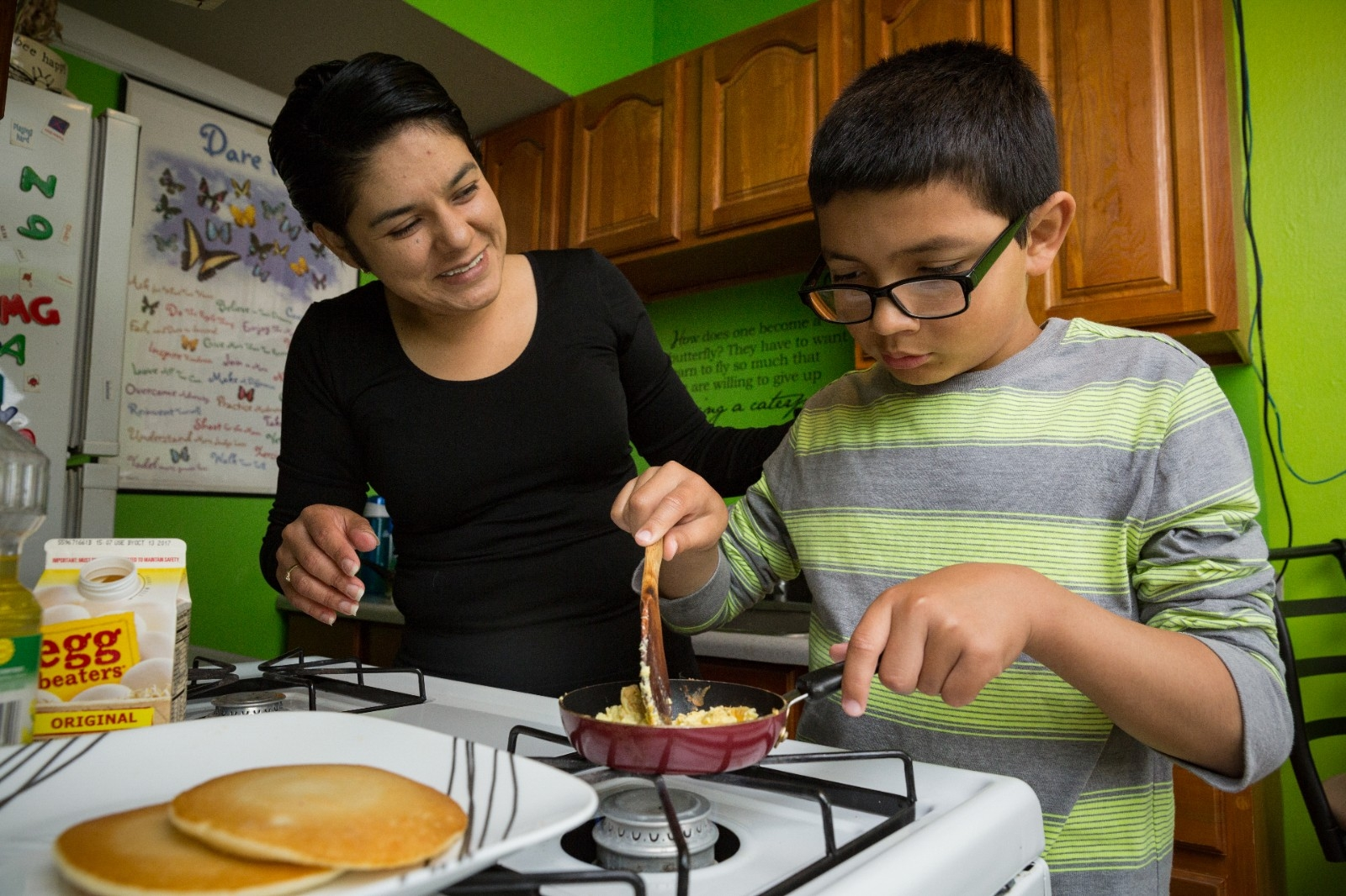 A mother gives her son a cooking lesson.