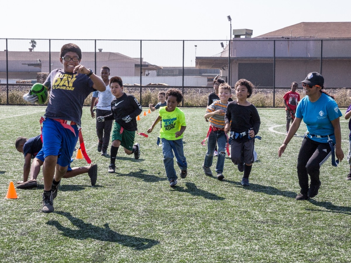 Children play flag football on an outdoor field.