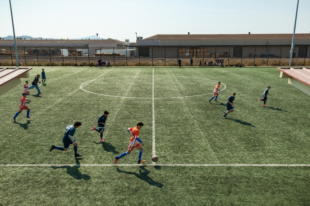Two teams play soccer on an outdoor field.