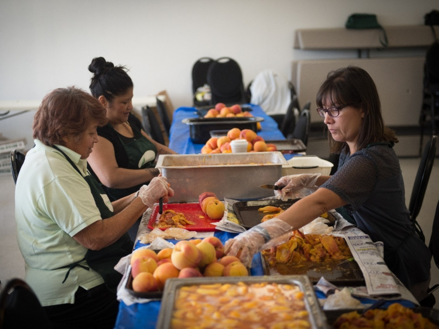Women peels peaches during a canning class.