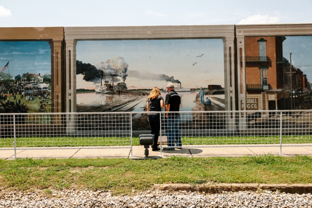 A couple stops to view a mural painted on a flood wall.