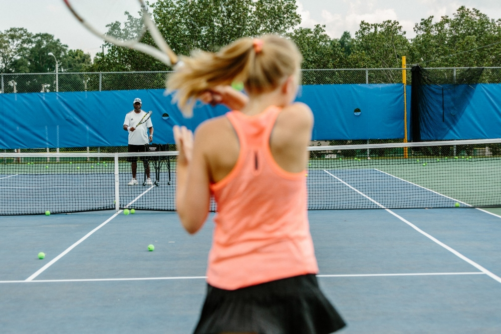 A tennis player practices tennis drills with her coach.