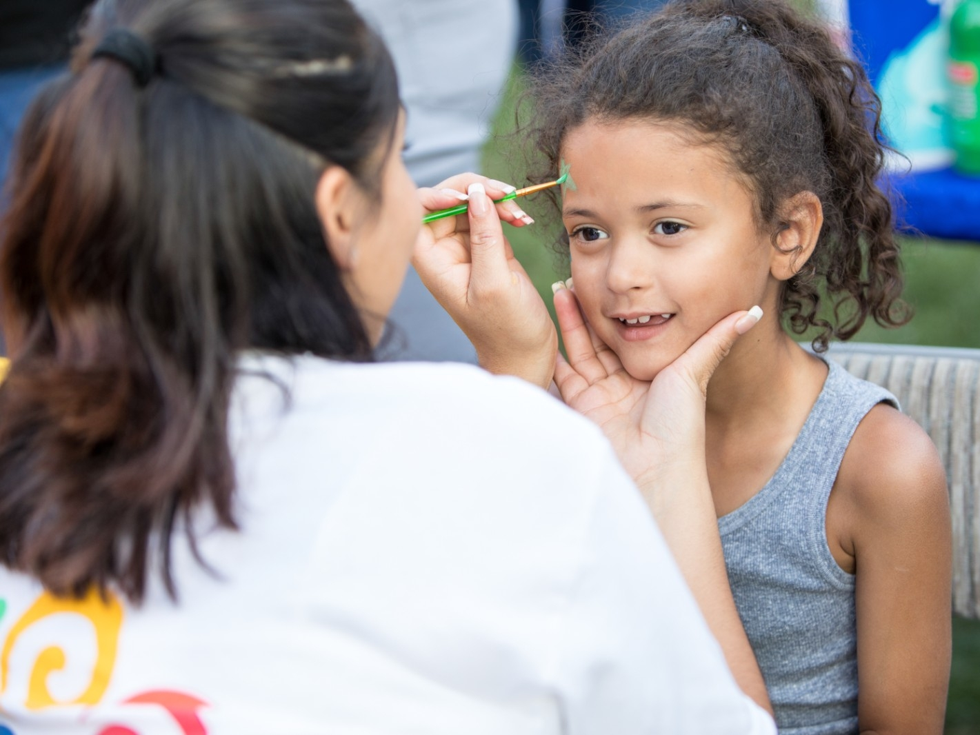 A young girl has her face painted at a community event.