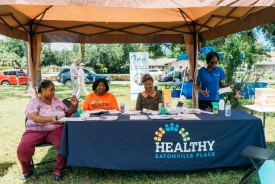 Women sit behind a booth at a health fair.