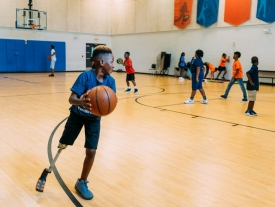 A boy with a prosthetic leg carries a basketball.