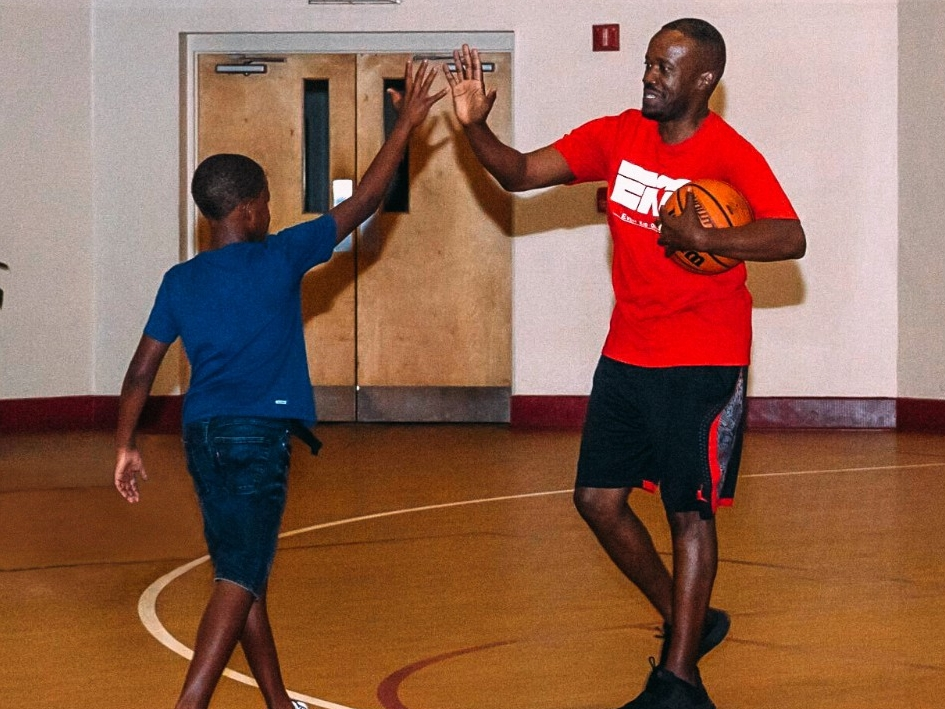 A man and boy high five in a school gym.