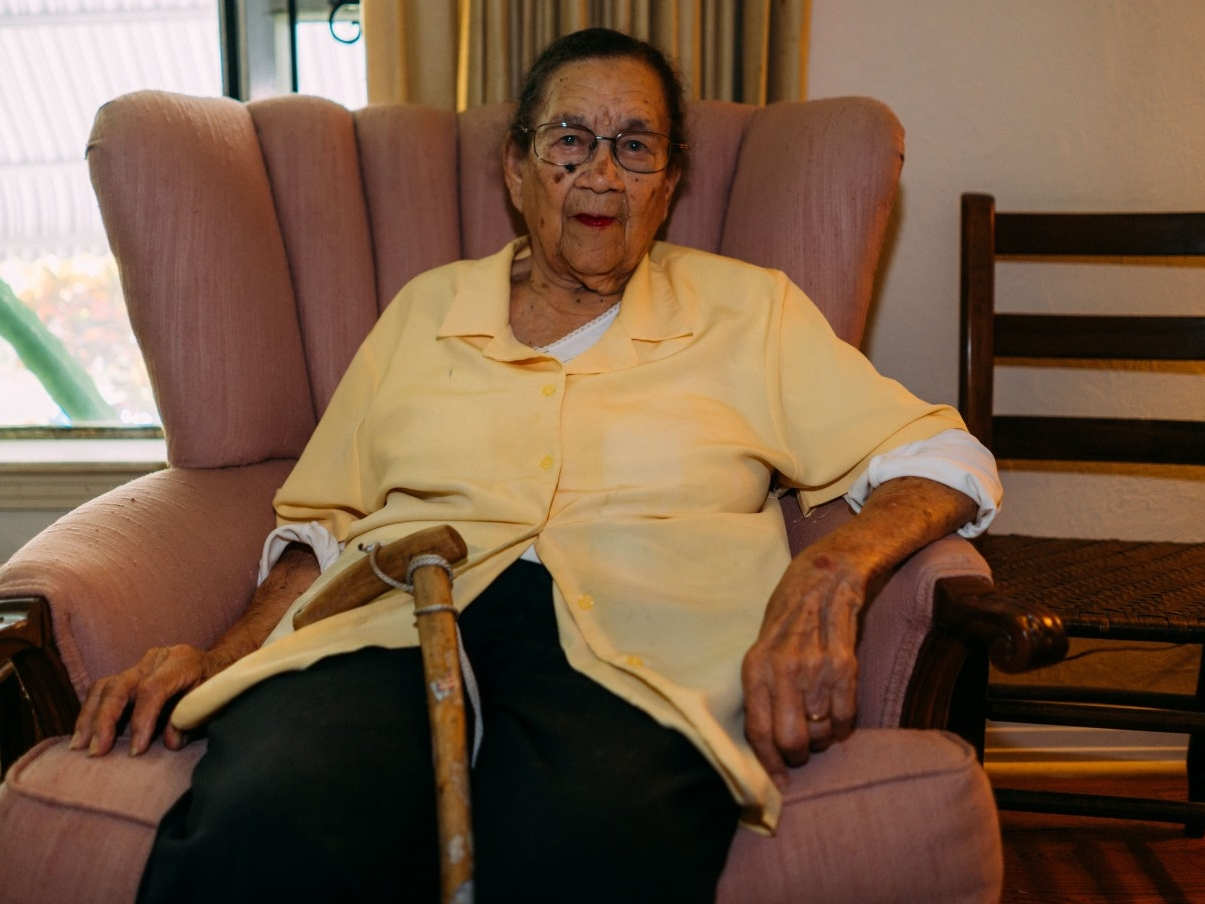 An elderly woman sits in a chair.