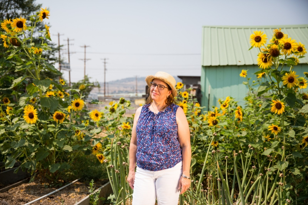 A woman in a straw hat stands among sunflowers.