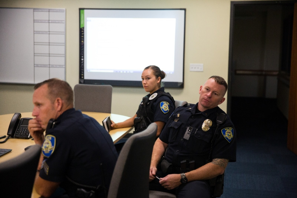 Police officers sit at a table during a meeting.