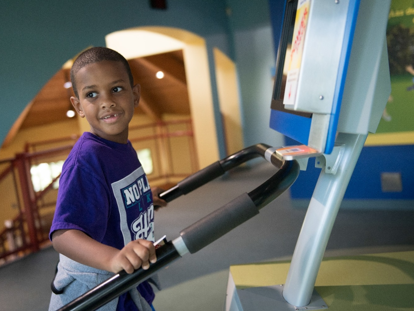 A young boy uses an interactive stair climbing station at a museum.