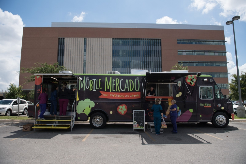 A mobile food bank in front of a hospital.