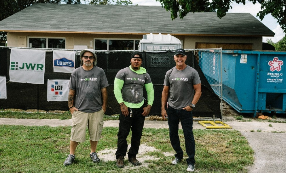 Men in front of a house being restored.