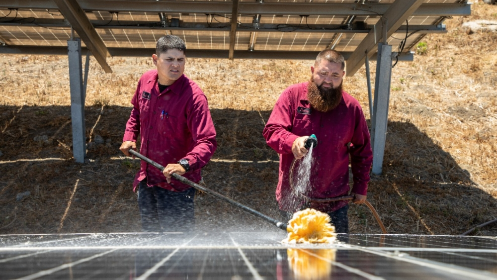 Tow men clean solar panels.
