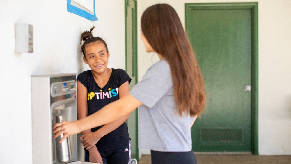 Two girls fill a water bottle at a school hydration station.