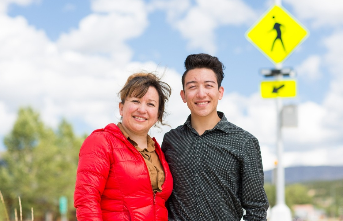 A mother and son stand in a pedestrian crosswalk.