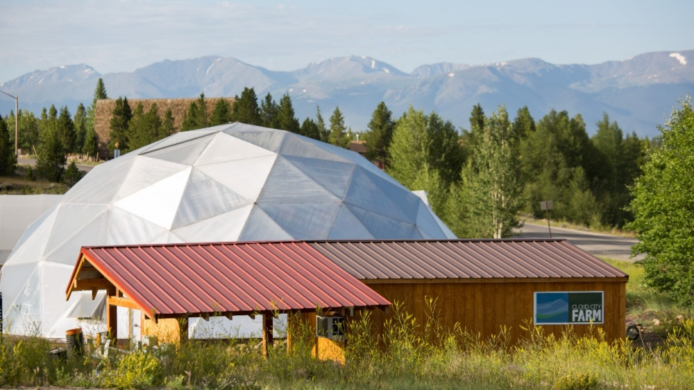 A farm with a dome growing house.