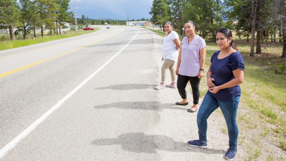 Three women stand on the side of a highway.