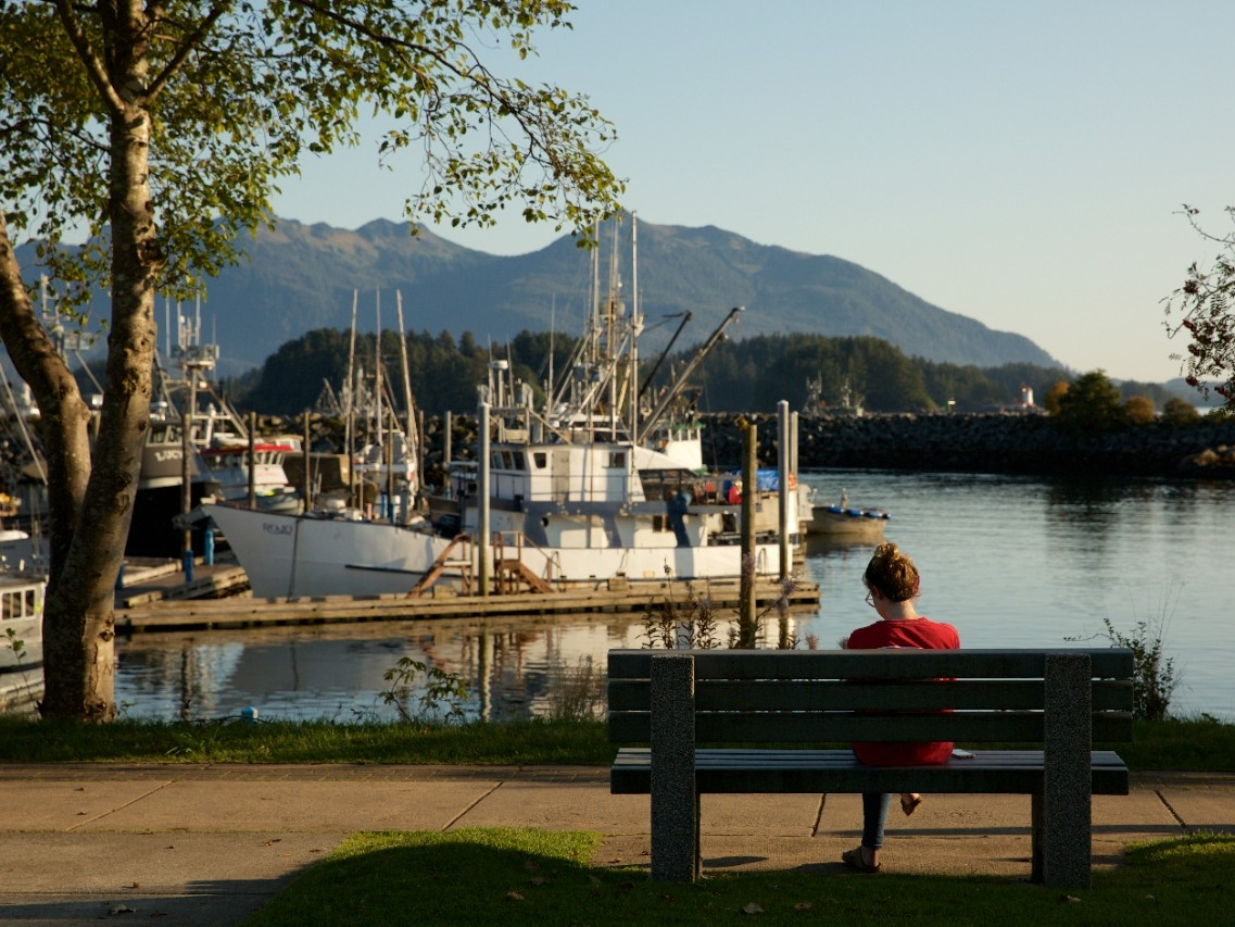 A woman sits on a bench overlooking a harbor.