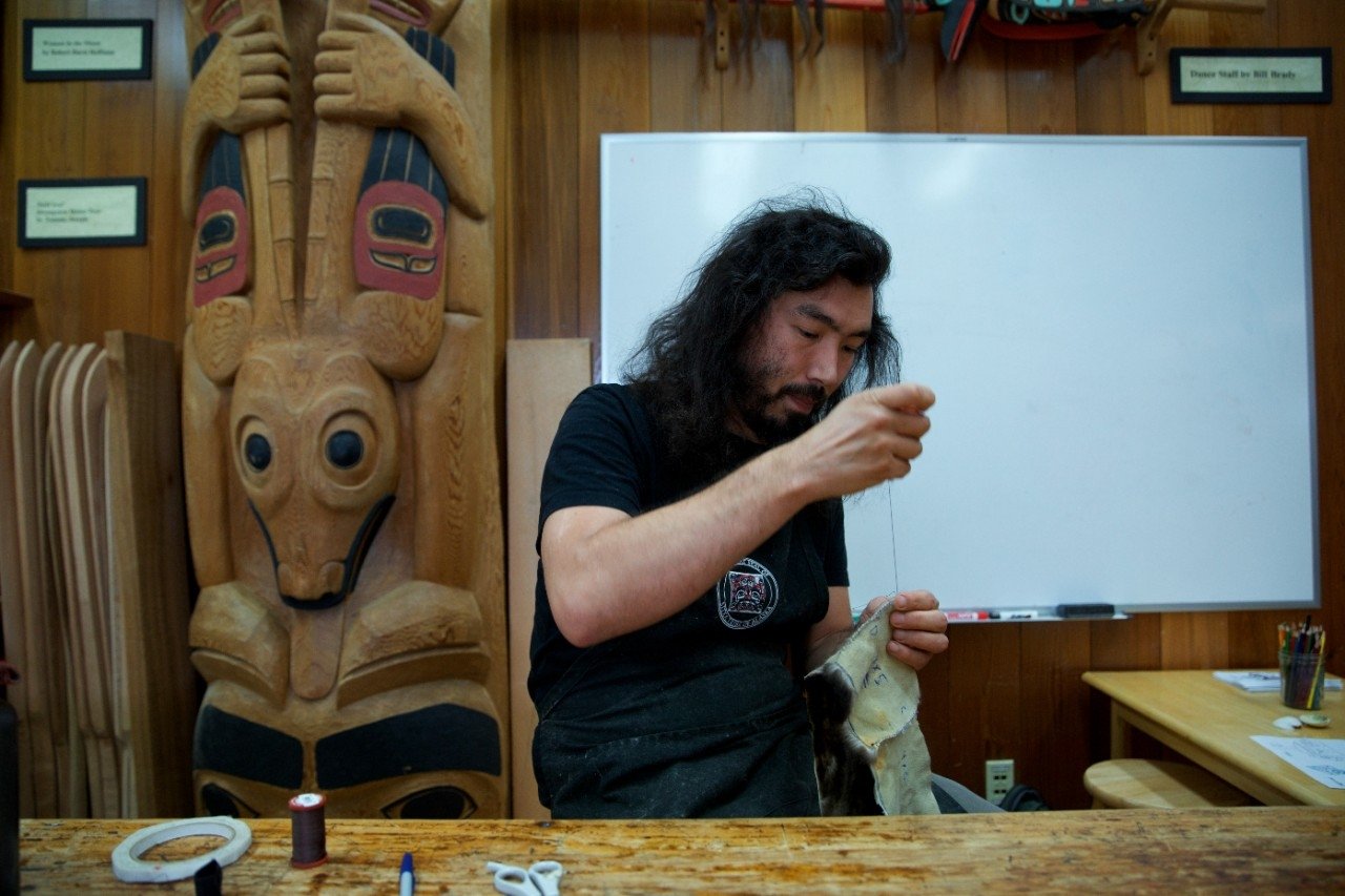 An artist works in his woodshop.