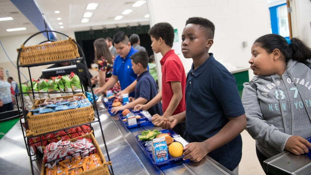 Students get lunch in a school cafeteria.