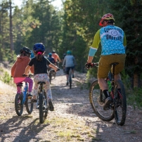 A family rides bicycles through a trail.