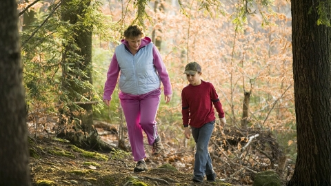 A mother and her son hiking through some woods.
