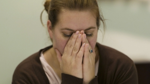 A woman with her hands over her face, reacting to something stressful.