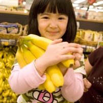 A small girl in a supermarket, holding a bunch of bananas