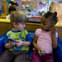 Young boy and girl play together in a classroom.