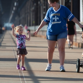 A mother and daughter use a pedestrian bridge.