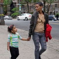 A woman walking along a city street holding a young girl's hand.