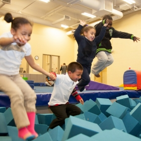Four energetic smiling kids jumping into a pit of foamy blocks.