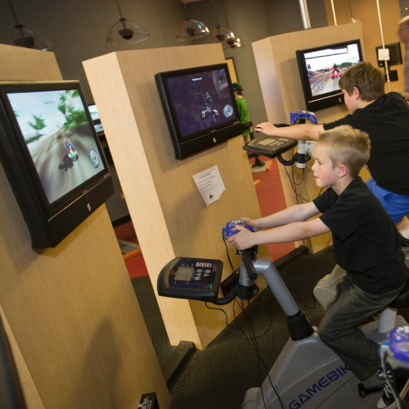Boys on exercise bikes playing an interactive physical activity game, in a fitness club.