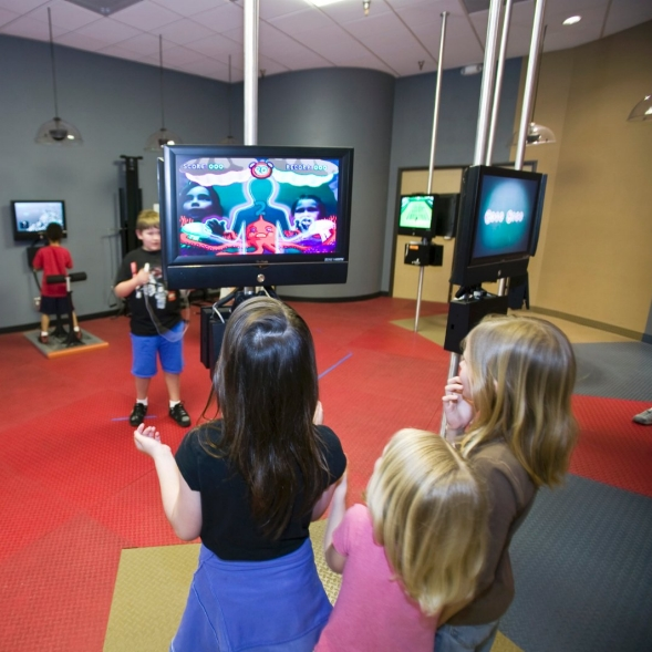 Children playing interactive physical activity video games at a fitness club.